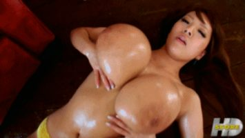 Hitomi Tanaka playing with her giant tits